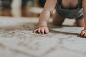 Ein Baby krabbelt auf einem Teppich