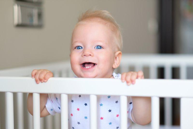 Ein glückliches Kind im Laufgitter