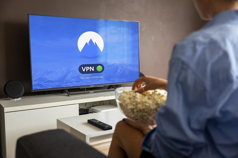 Ein Mann mit Popcorn blickt auf einen Fernseher mit VPN-Verbindung
