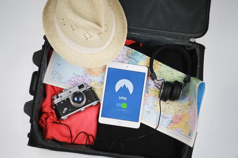 Ein Koffer mit Ausrüstung für den Urlaub und einem Smartphone mit VPN-Verbindung
