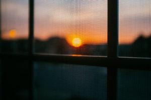 Fliegengitter am Fenster beim Sonnenuntergang