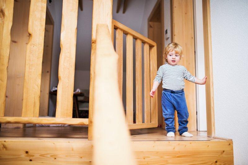 Junge steht bei Treppenschutzgitter