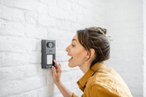 Frau spricht in eine Türsprechanlage hinein.