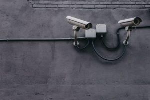 Überwachungskamera, welche außen an der Wand angebracht ist.