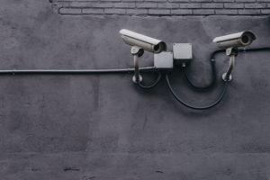 Überwachungskameras mit Arm vor einer Betonwand